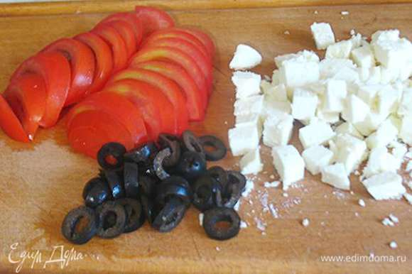 Помидоры крупные порезать полукольцами, маслины кружочками, а фету порезать на небольшие кусочки.