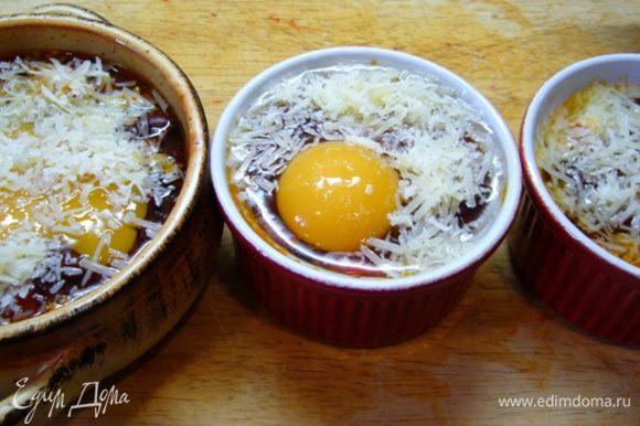 Керамические формочки смазать оливковым маслом, выложить томатно-фасолевый соус, сверху разбить яйцо, посыпать тертым сыром. Отправить в духовку, разогретую до 200 град. на 12 мин.