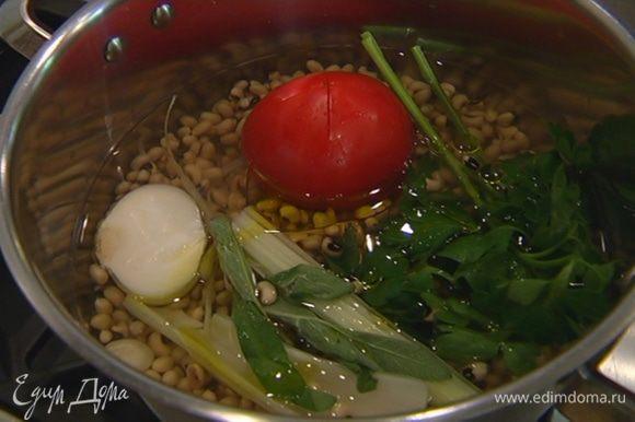 В кастрюлю налить 600 мл холодной воды, опустить в нее фасоль, сельдерей, лук, морковь и неочищенный помидор целиком, добавить пучок петрушки, зубчик чеснока в шелухе, 1 ст. ложку оливкового масла лавровый лист и черный перец горошком. Не солить! Варить фасоль вместе с овощами до готовности.