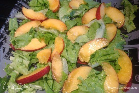 Листья салата вымойте, обсушите бумажным полотенцем, порвите, выложите на блюдо. Сверху выложите нектарины.