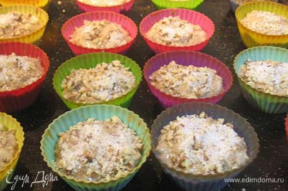 Заполнить формочки на 2/3 и сверху посыпать смесью из сахара и орехов.