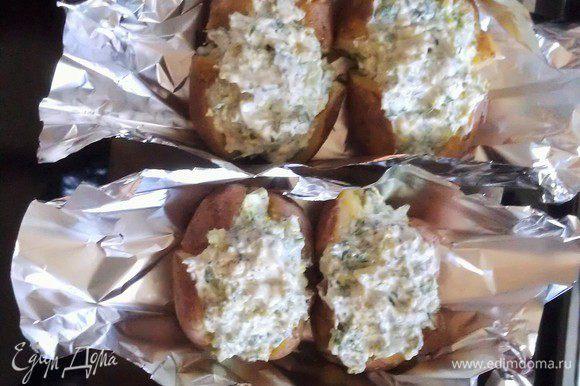 Из фольги вырезать прямоугольники и сделать порционные лодочки, защипнув края с двух сторон. Выложить в каждую по две картофелины, слега их посолить и сбрызнуть оливковым маслом, начинить творожно-овощной смесью. На донышко каждой лодочки налить по ложечке оливкового масла.