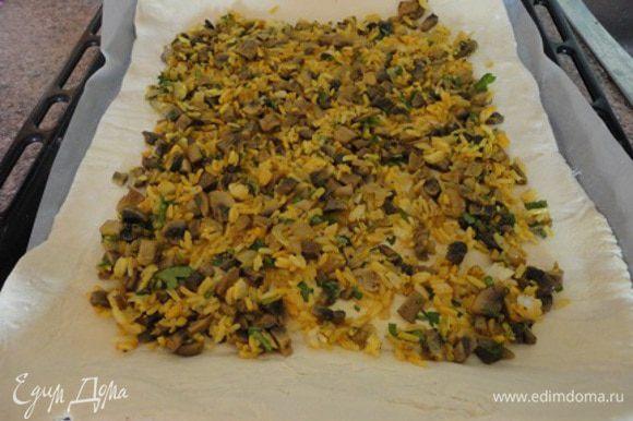 Рис отварить до готовности, воду слить. Лук нарезать мелкими кубиками, шампиньоны нарезать пластинами или кубиками и спассеровать на сливочном масле до золотистого цвета. Лук, шампиньоны соединить с рисом и рубленной зеленью (вместо петрушки можно взять укроп, или все вместе - дело вкуса), посолить, поперчить по вкусу, приправить куркумой и хорошо перемешать. Филе рыбы вымыть, обсушить и нарезать большими кусками. Я только отделила филе от кости и оставила целыми кусками. Филе посолить, поперчить по вкусу и полить соком лимона. Тесто разморозить при комнатной температуре и раскатать в два прямоугольных листа. Я на двойную ному всех продуктов использовала три листа слоеного теста. Лист для выпекания выстлать бумагой и на него выложить один пласт теста. На него выложить половину начинки.