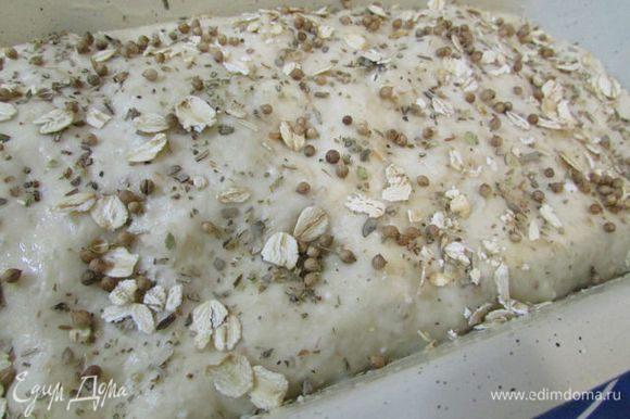 Разогрейте духовку до 190 градусов. Сбрызните хлеб водой и посыпьте сухими травками и овсяными хлопьями (это по желанию). Поставьте в духовку. Выпекайте 40 минут. Готовность проверяйте лучинкой, она должна выходить из буханки сухой.