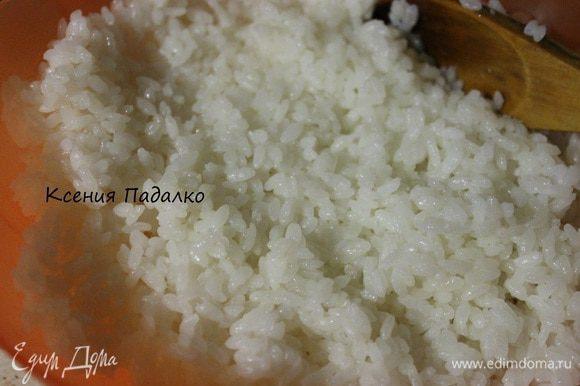 Смешать уксус, сахар и соль и подогреть в микроволновке. Перемешать, чтобы сахар и соль растворились. Далее рис переложить деревянной лопаткой в широкую миску, добавить к нему уксус с сахаром и солью, и резкими режущими движениями перемешать. Оставить остывать.