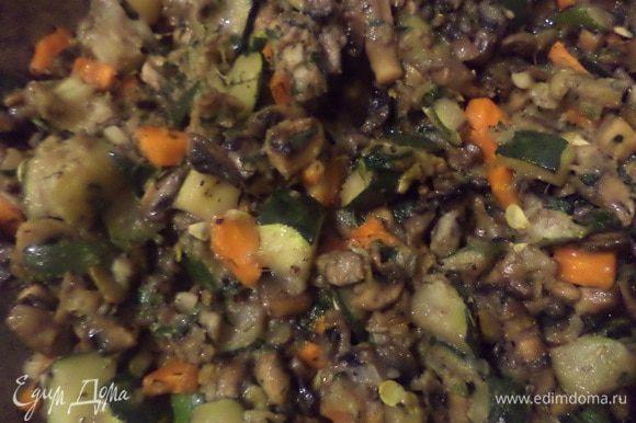 Лук обжарить на растительном масле до прозрачности. До бавить шампиньоны, посолить, поперчить, обжарить грибы с луком. Теперь добавить морковь и цуккини, тушить, пока не выпарится жидкость. Добавить измельчённый чеснок, мелко рубленную зелень, половину тыквенных семечек, прованские травы, муку, перемешать.