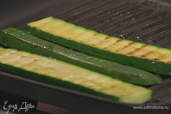 Разогреть в сковороде-гриль 1 ч. ложку оливкового масла и обжарить ломтики цукини.