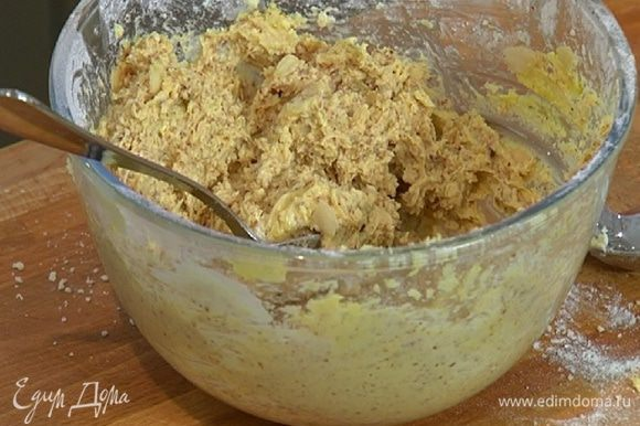 Добавить оставшуюся миндальную крошку, лепестки миндаля, влить миндальный и ванильный экстракт, ром и вымешать все ложкой в однородную массу.