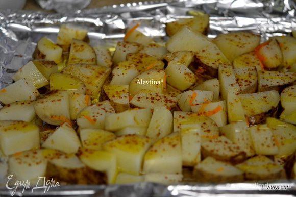 Противень застелить бумагой для выпечки, вылить оливковое масло и поставить в горячую духовку на 5 мин. Затем выложить на горячий противень картофель, перемешать с горячим оливковым маслом. Посолить, посыпать куркумой и паприкой и вернуть в духовку на 1 час.