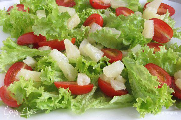 Салатные листья нарвать руками и выложить на блюдо. Можно использовать любой зеленый листовой салат, в том числе и пекинскую капусту. Добавить ананасы и помидоры.