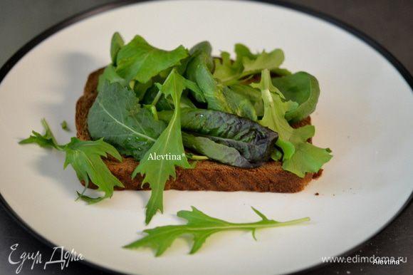 На хлеб свежий или разогретый в тостере выложить мягкое масло по желанию, затем свежие листья салата.