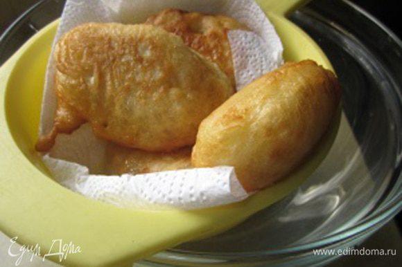 Готовые пончики выкладываем в ситечко, застеленное бумажным полотенцем. Все-таки маслица на них много, пусть хоть немного да промакнутся.