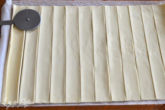 Готовое слоеное тесто развернуть и нарезать полосками шириной 2,5 см.