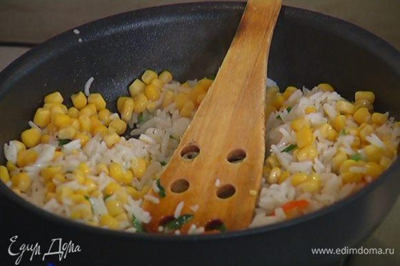 Добавить к луку с чили готовый рис, посолить, поперчить и обжарить, затем добавить кукурузу, все перемешать.