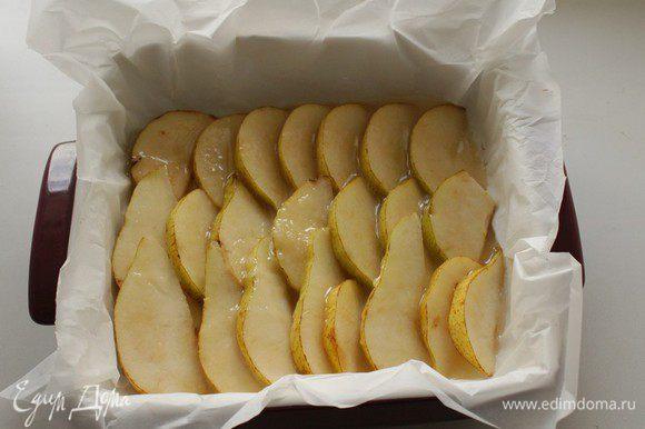 Выстелить форму для выпечки пергаментом, выложить разрезанные дольками груши , равномерно полить карамелью