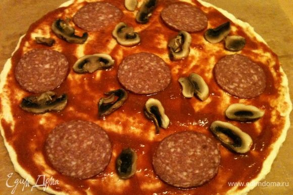 Уложить на соус все тонко нарезанные продукты - колбасу, грибы .