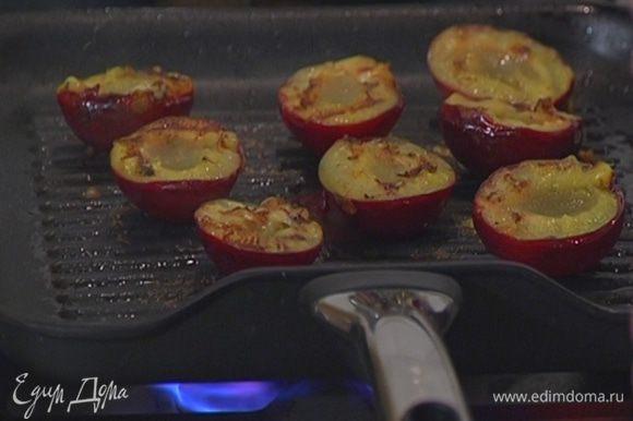Из сковороды слить лишний жир, уложить в нее сливы срезами вниз и обжаривать до появления золотистых полосок.