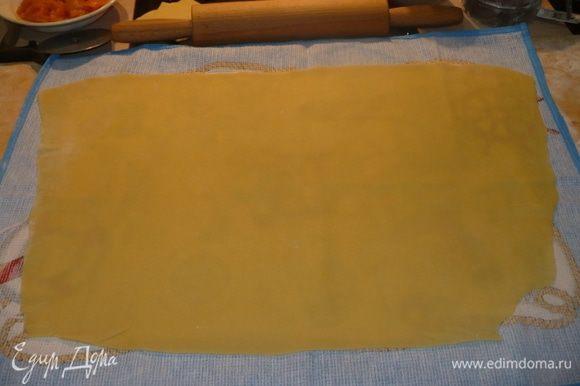 Перекладываем пласт теста на салфетку или полотенце, чтоб легче его скручивать было.