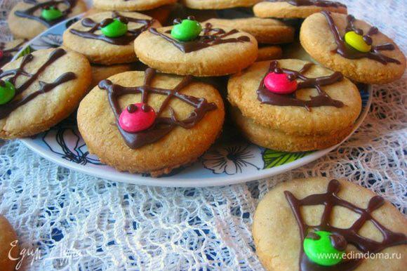 Разукрасить каждое печенье, в виде паутины. На шоколад приклеить М&M's и нарисовать на них глазки.