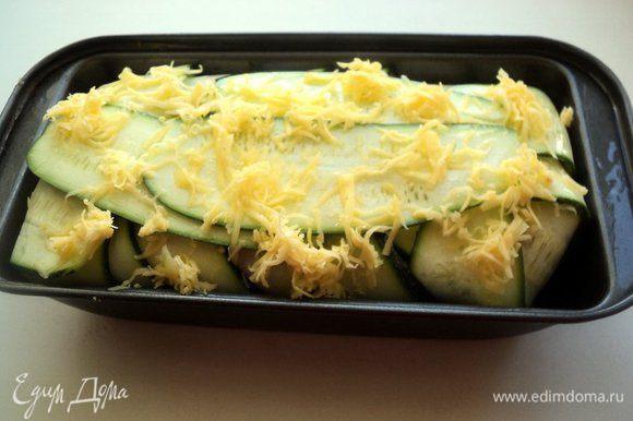 Выложить в форму фарш, хорошо уплотнить ложкой. Накрыть фарш свисающими пластинками кабачка. Смазать сверху растительным маслом и слегка присыпать тертым сыром.