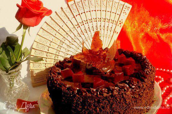 Обсыпать бока торта крошкой из бисквита. Оставшейся глазурью украсить верх торта с помощью кондитерского шприца. Украсить торт кубиками желе из красного сладкого перца и малины и фигурками из карамели.