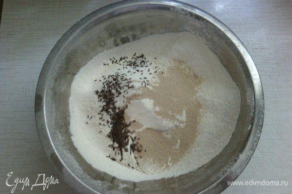 В большую миску просейте оба вида муки, добавьте соль, дрожжи, тмин и перемешайте.