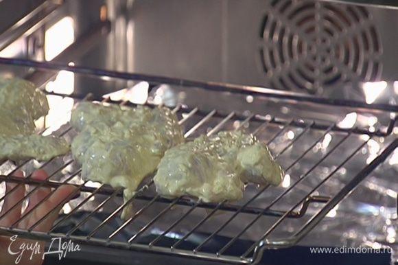 Замаринованные куриные грудки выложить на решетку, смазать остатками маринада и поместить в духовку на средний уровень.