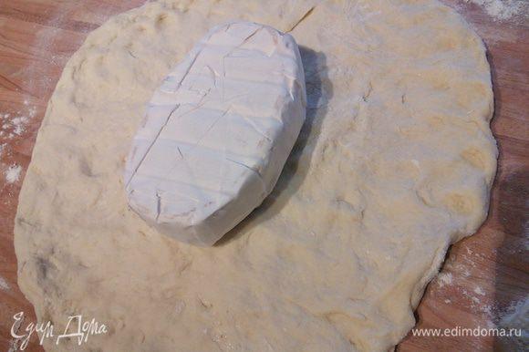 В любом случае выложите тесто на посыпанную мукой рабочую поверхность. Распластайте его руками. Выложите сыр ( он должен быть продолговато-овальной формы).