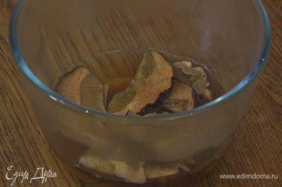 Сухие грибы замочить в кипятке, дать настояться, затем слить воду через сито в отдельную посуду.