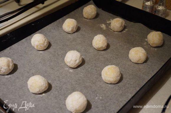 Скатываем шарики, обкатываем в сахарной пудре, выкладываем на пергамент и печем минут 11-14. Остужаем на решетке