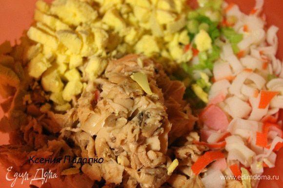 Разделить яйца на белки и желтки. Белки отложить. Желток и крабовые палочки нарезать кубиками, с рыбы слить жидкость и слегка размять ее вилкой, убрав все кости. Зеленый лук мелко нарезать. Белки и морковь натереть на мелкой терке в разные тарелки.