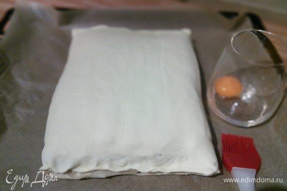Заверните рулет в тесто, защипните краешки теста. Смажьте желтком.