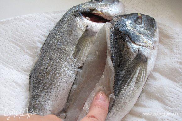 Раздвинуть мясо руками и удалить хребет вместе со спинным плавником и реберными костями с помощью ножниц. Через спинку очистить рыбу от внутренностей и тщательно вымыть снаружи и внутри.