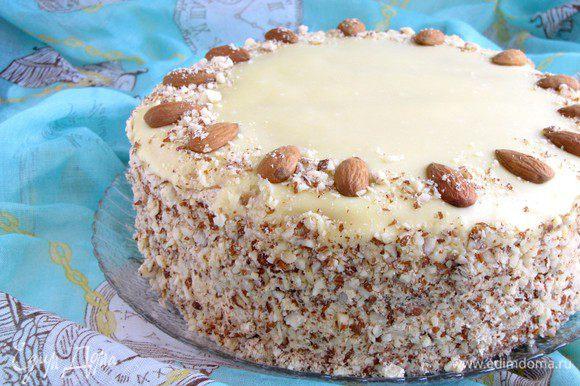 Сверху аккуратно вылить на торт еще теплую глазурь. Кулинарной лопаткой разровнять поверхность. Бока торта обсыпать миндальной крошкой, по желанию. Украсить торт орешками. Убрать в холодильник для охлаждения часа на два.