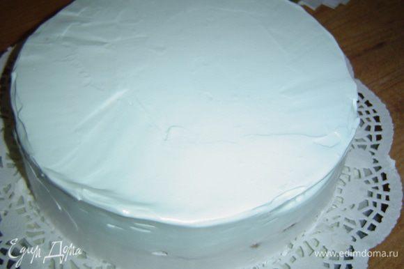 Взбиваем сливки с сахарной пудрой до устойчивых пиков, добавляем черничный джем и перемешиваем. В результате получаем нежный голубой цвет. Эти сливки наносим на бока и верх торта, ровняем.