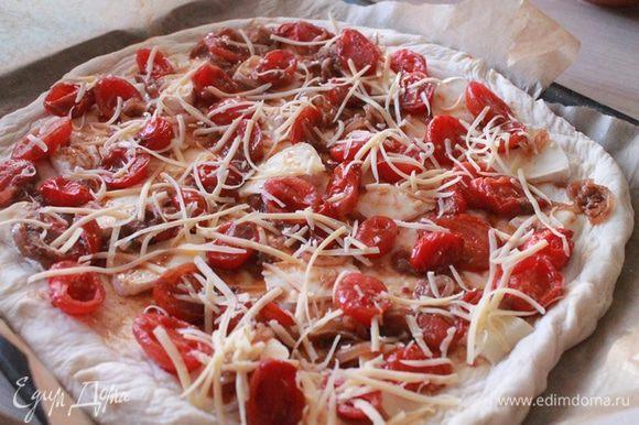 Возьмите большой противень или круглую большую форму. Выложите пекарской бумагой и растяните тесто руками придав круглую форму лепешке. Сверху выложите сыр и залейте соусом.