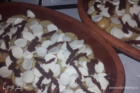 Тарелки смазываем маслом от томатов, выкладываем слой картофеля, слой моцареллы и томаты, немного солим.