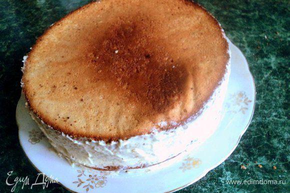 Накрыть вторым коржом. Смазать корж половиной крема, накрыть третьим коржом и оставшимся кремом смазать бока торта.
