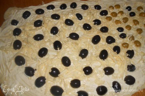Раскатать тесто не очень тонко. Поверхность смазать маслом. Выложить оливки и маслины на тесто, посыпать тертым сыром и травами.