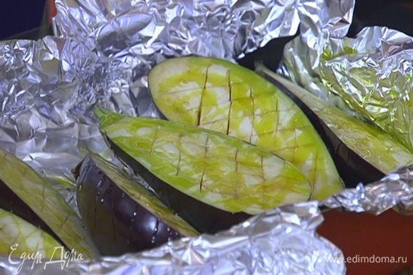 Глубокий противень выстелить пищевой фольгой, выложить баклажаны срезами вверх, полить 3‒5 ст. ложками оливкового масла, посолить, поперчить и запекать в разогретой духовке 15–20 минут.