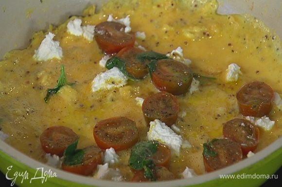 Козий сыр небольшими кусочками разложить на омлет, сверху выложить припущенные помидоры с базиликом.