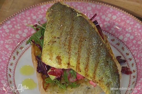 Сбрызнуть тосты оставшимся оливковым маслом Extra Virgin, выложить на них салат, а сверху рыбу.