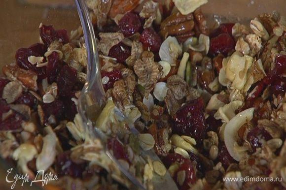 Мюсли соединить с клюквой и орехами, посолить, добавить растопленное масло, все перемешать.