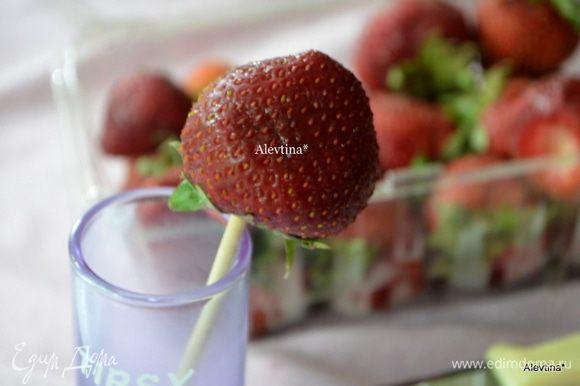 Насаживаем аккуратно промытую клубнику по центру на шпажку. Для удобства ставим в высокую рюмку. Зеленую плодоножку желательно оставить на ягоде.