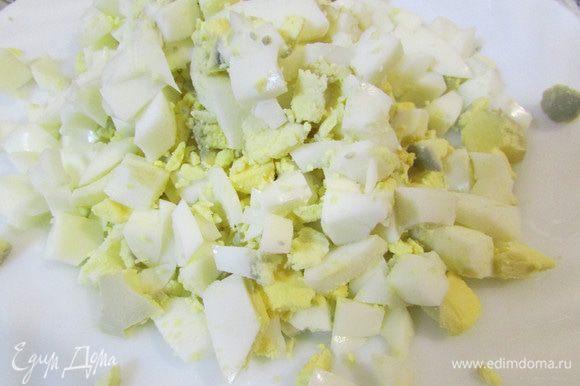 Яйца отварить, залить холодной водой. Затем почистить, порезать кубиками.