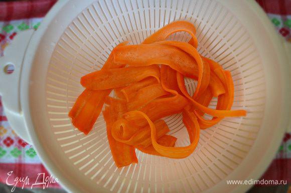 Затем слить горячую воду и залить ледяной водой, либо выложить морковные ленты на лёд.