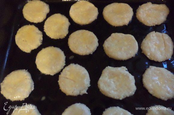Колбаски нарезать кружочками толщиной 3 - 4 мм, выложить на противень и смазать желтком.