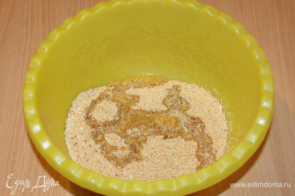 Печенье измельчите в мелкую крошку, перемешайте в миске с растопленным маслом.
