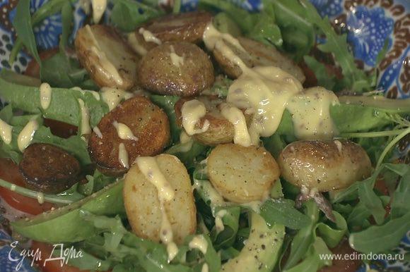 На салат выложить теплый картофель, посолить, поперчить и слегка полить майонезом.