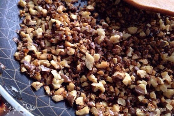 Орехи измельчить ножом. Затем прожарить минуту-две на раскаленной сковороде, добавить 2 чайные ложки сахар и еще прожарить 1-2 минуты. Добавить остывшие орехи к бисквитной крошке.